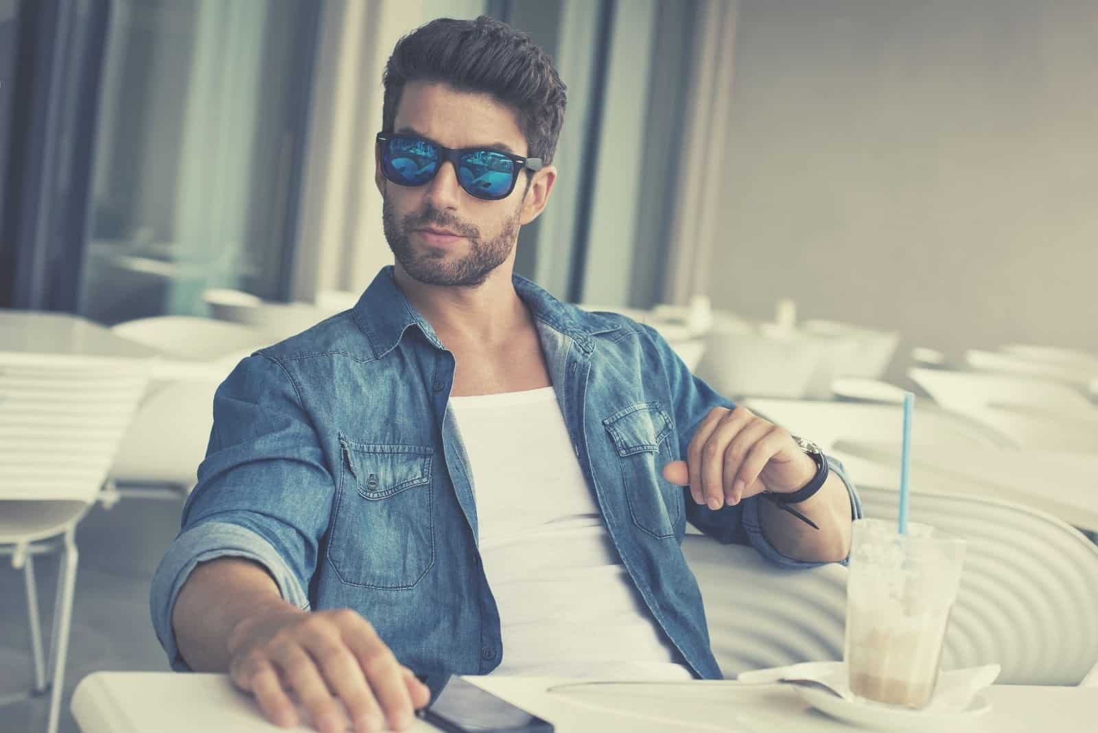 young handsome man sitting in the table wearing shades