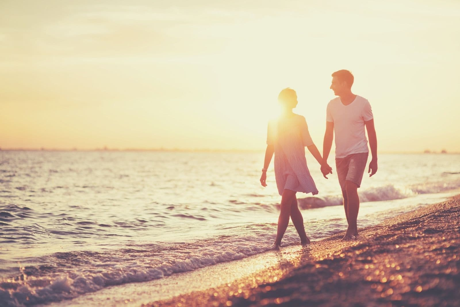 young happy couple on seashore walking while holding hands and talking