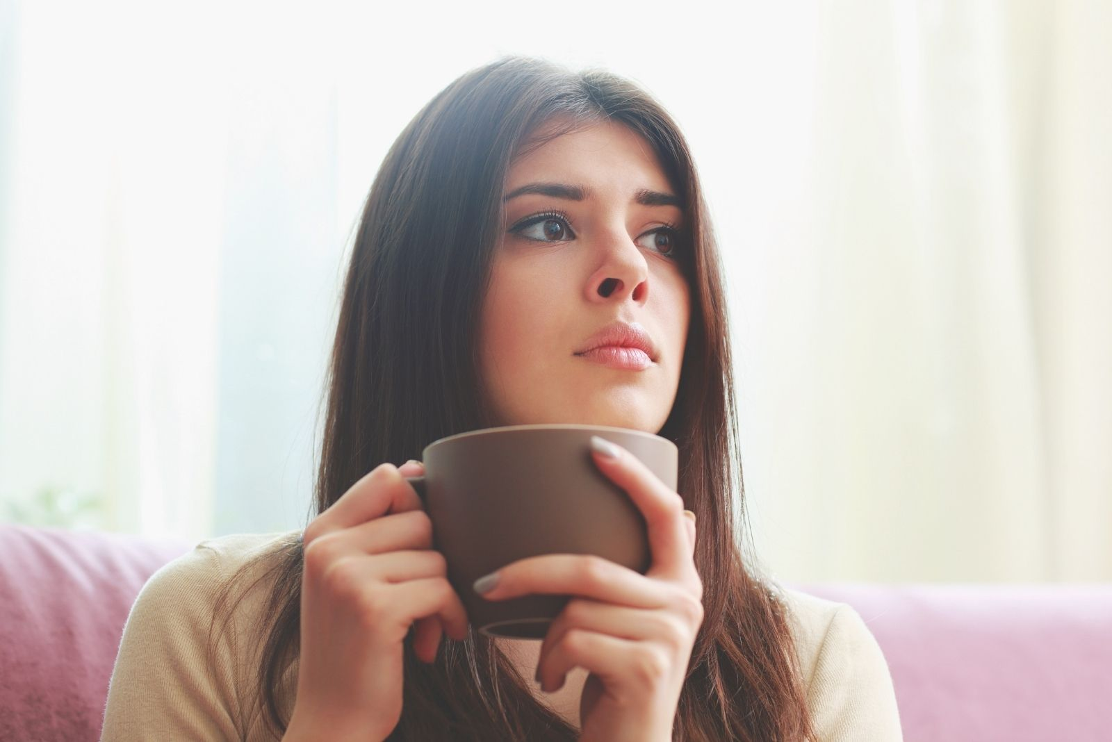 young hispanic pensive woman looking away while holding a cup of beverage
