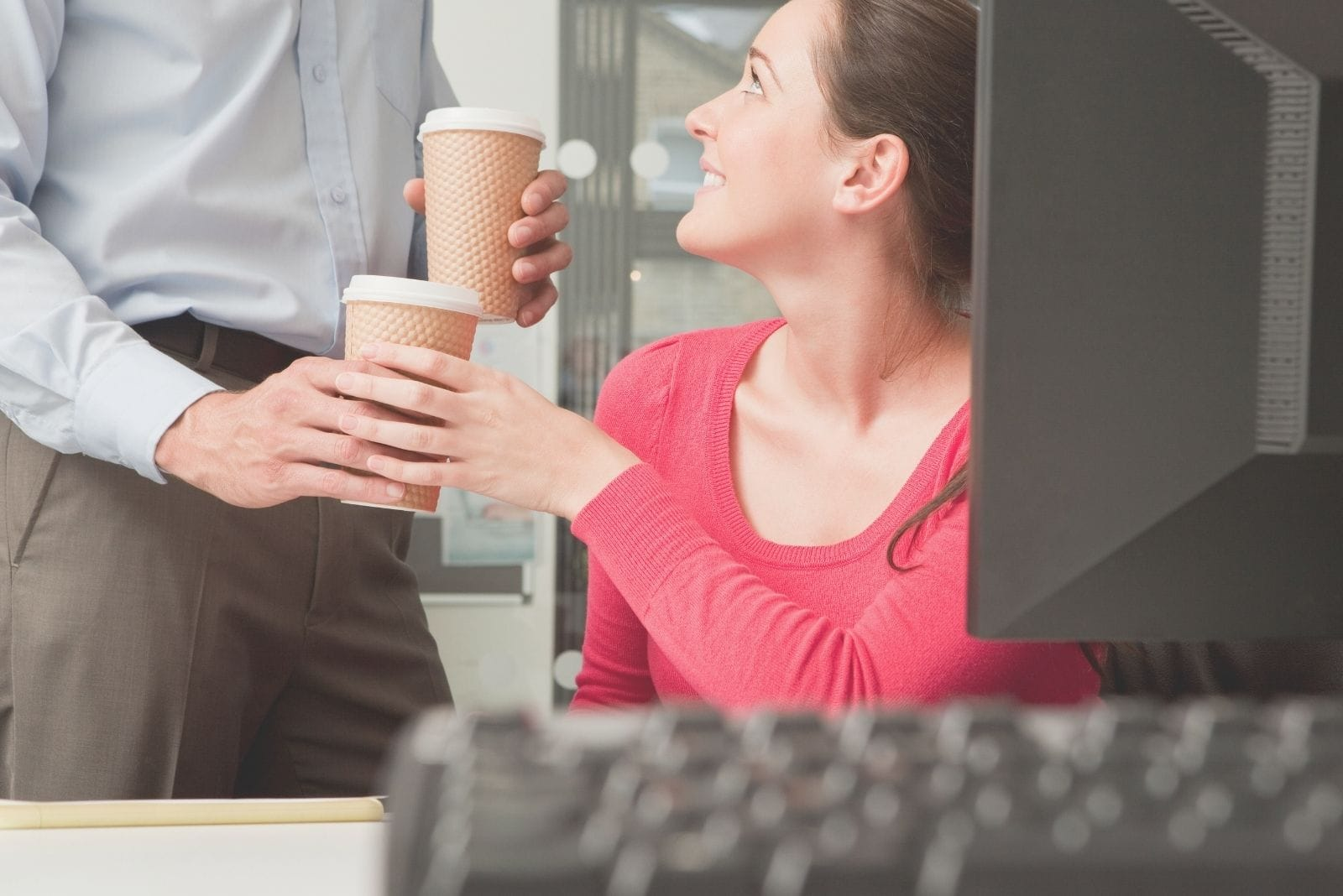 young man giving coffee to his colleague in the office
