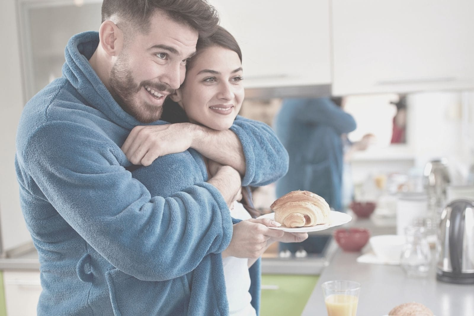 young man hugging wife in the kitchen bring baked bread