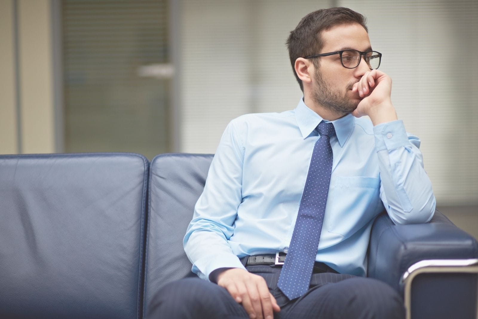 young pensive businessman sitting in the sofa inside livingroom