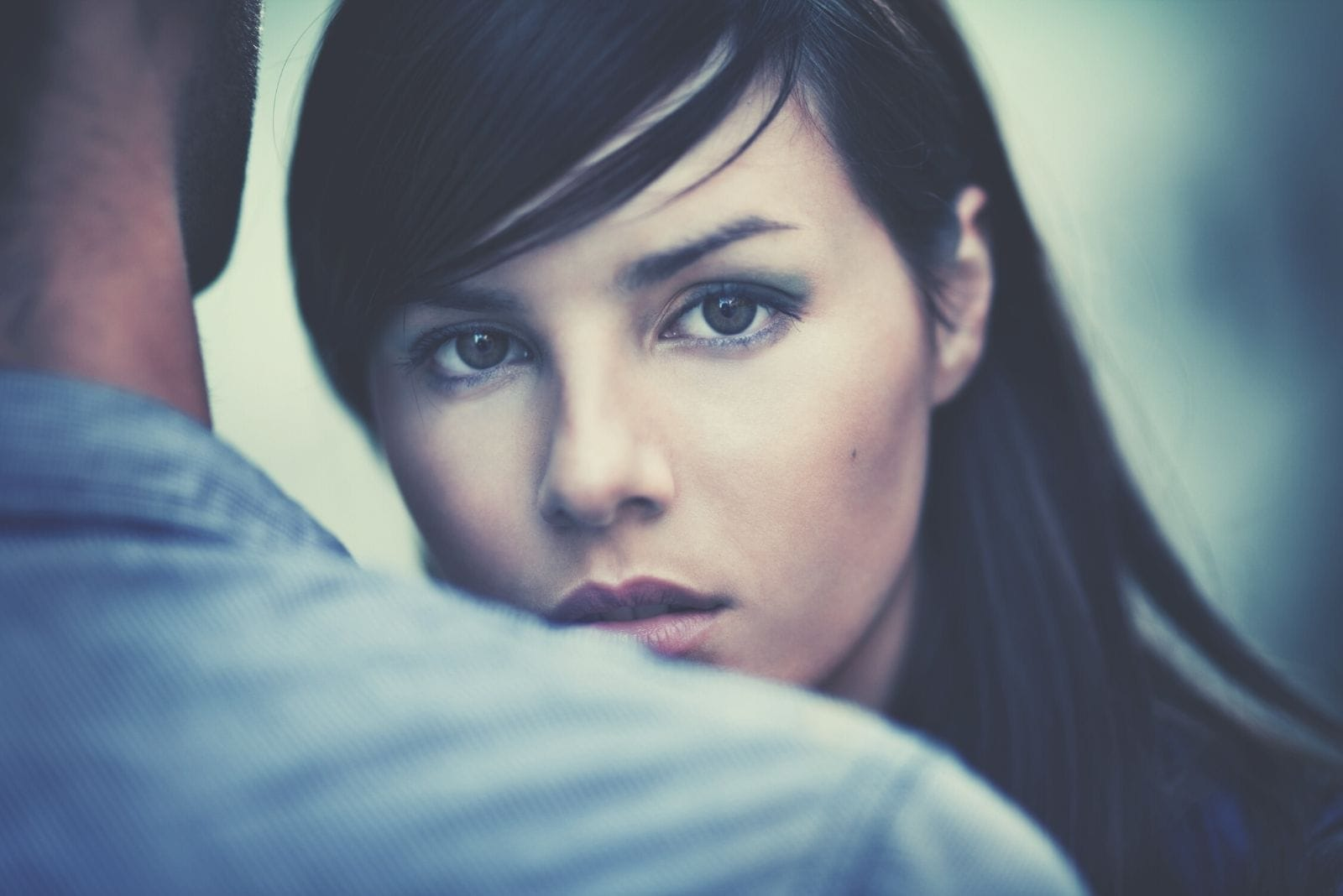young pensive woman staring at the camera over a man's shoulder