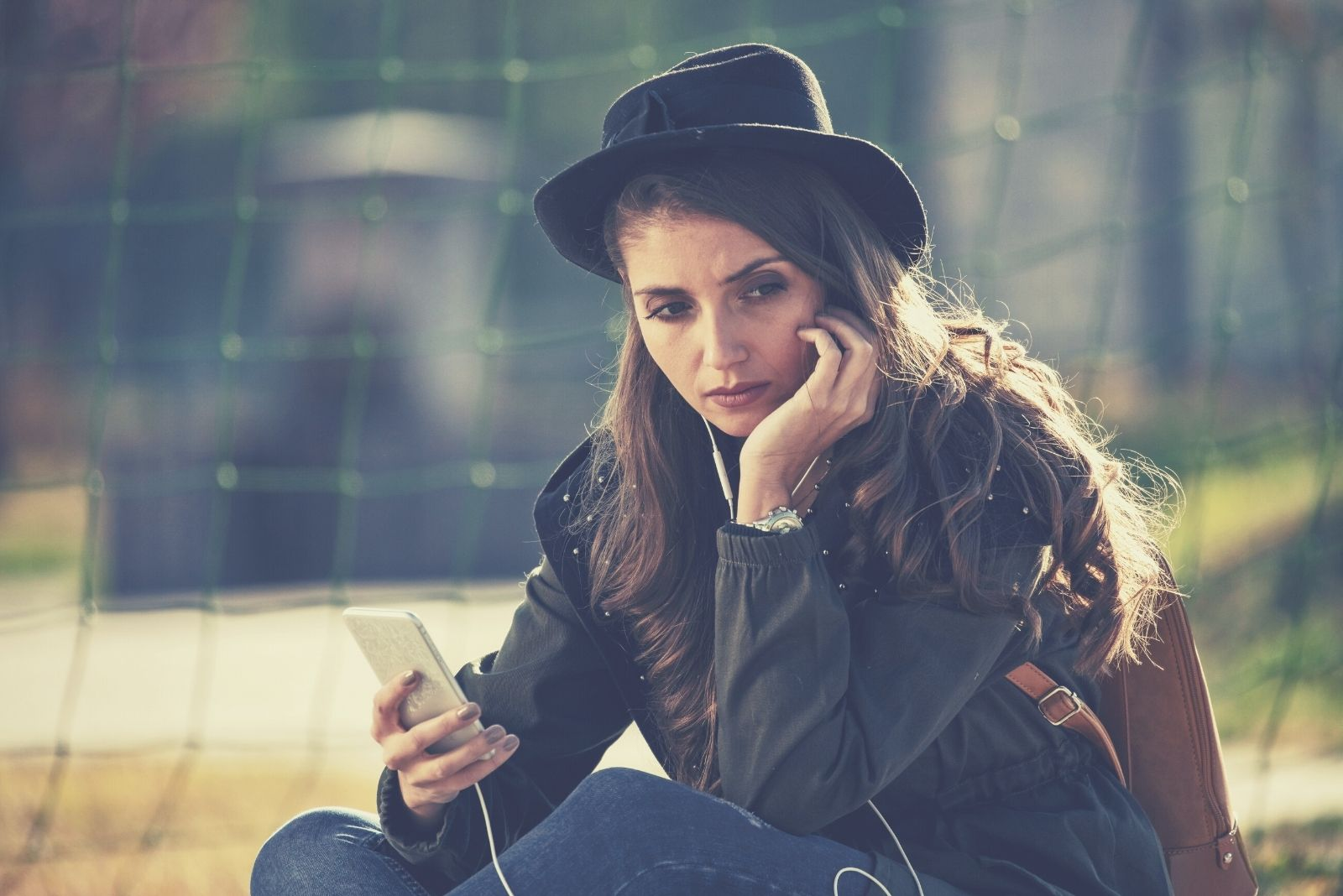 young sad woman with a phone sitting outdoors with a hat