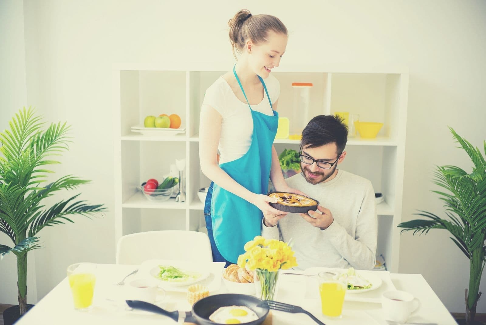 young wife serving food to her husband in the dining room