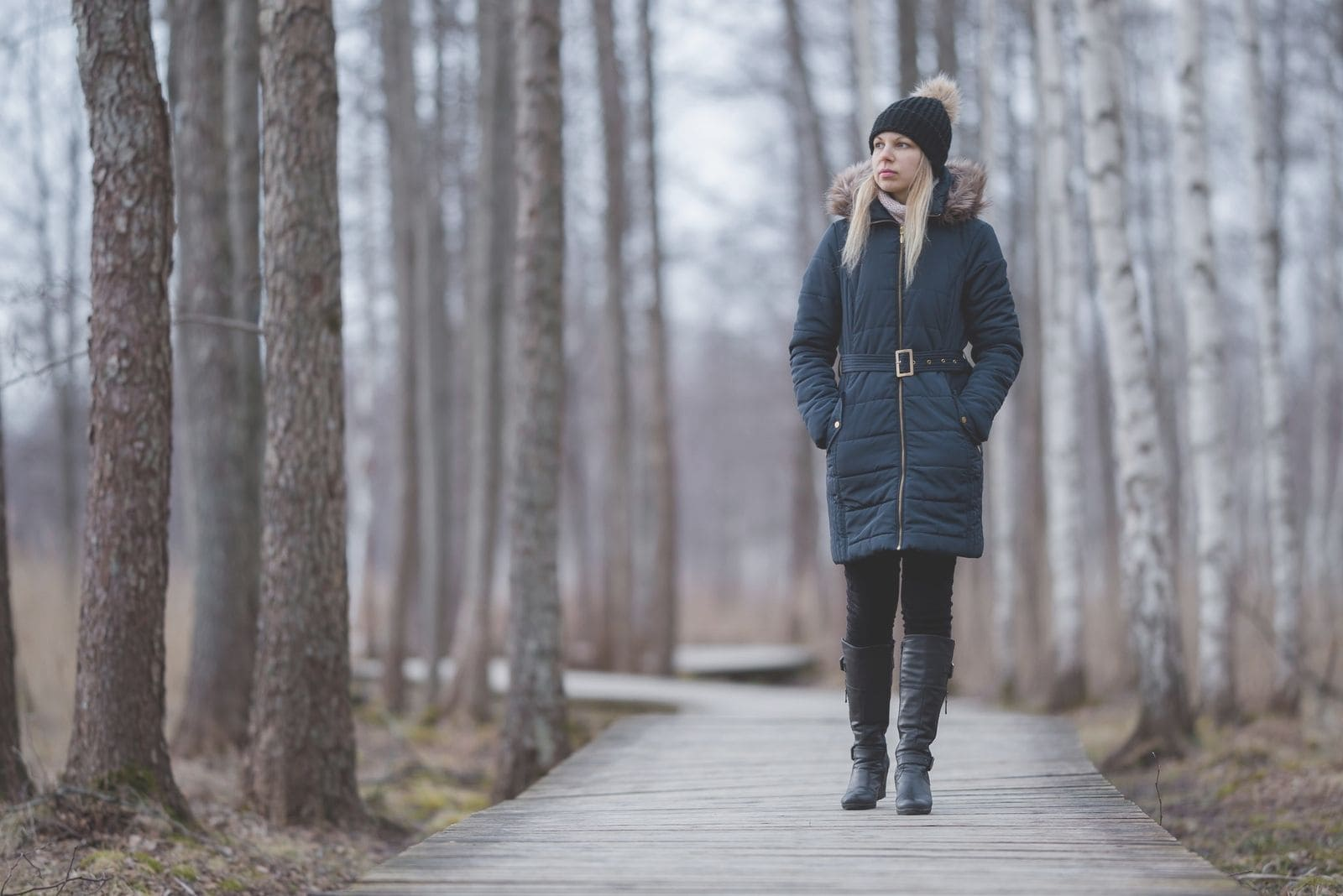 young woman in dark warm clothes walking in wooden trail of a peaceful park