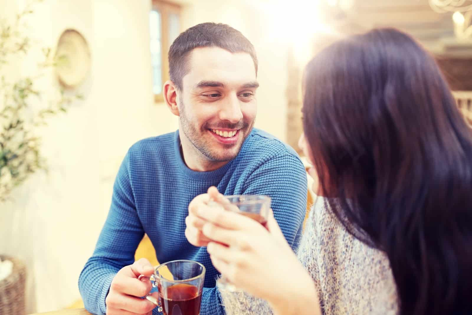 happy man and woman drinking tea while sitting in cafe