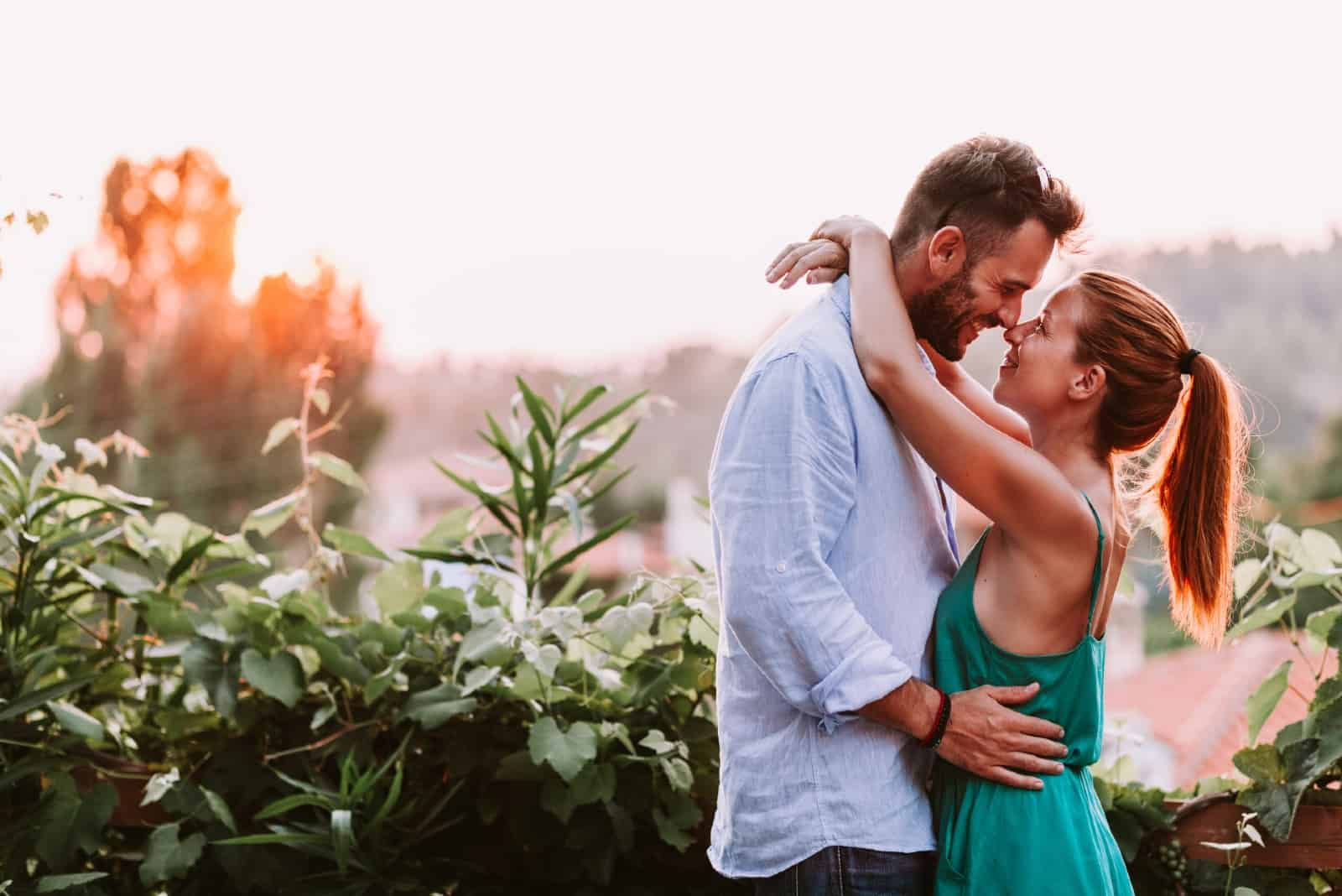 man and woman hugging while standing near plants