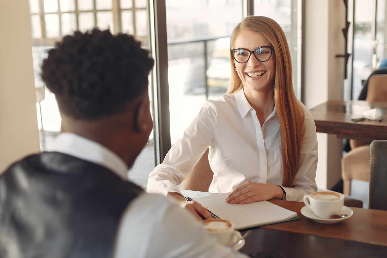 happy woman in white shirt looking at man while sitting in cafe