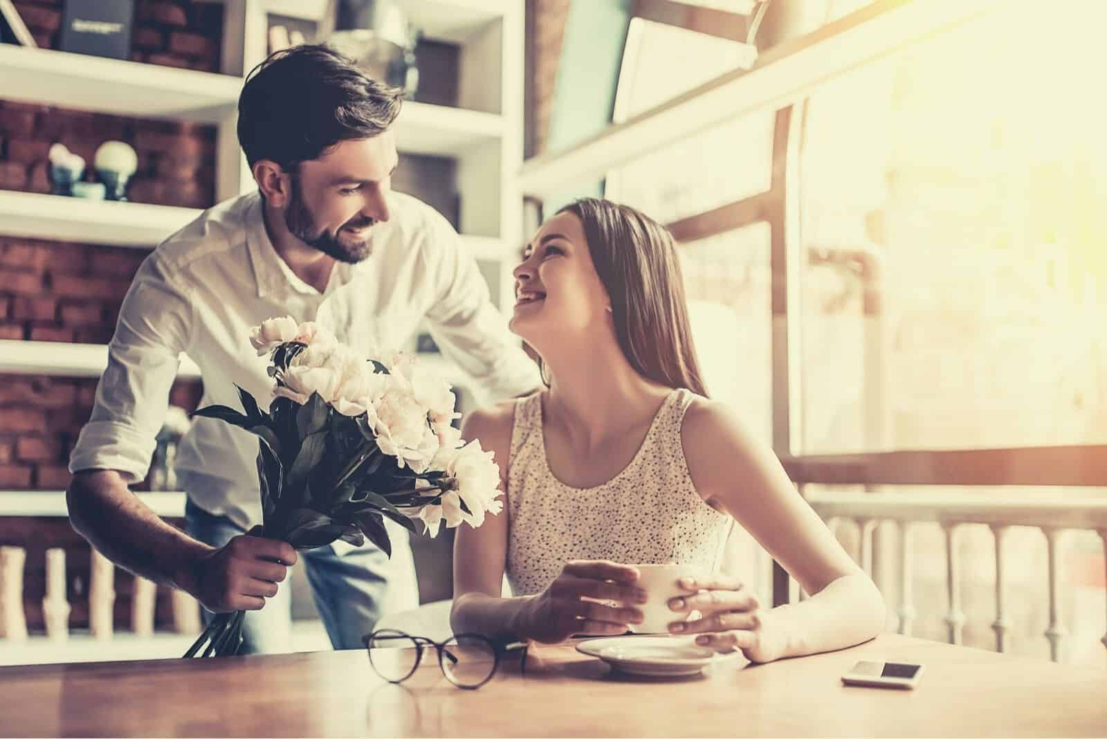 woman surprised by the flowers given by her boyfriend while waiting inside a cafe