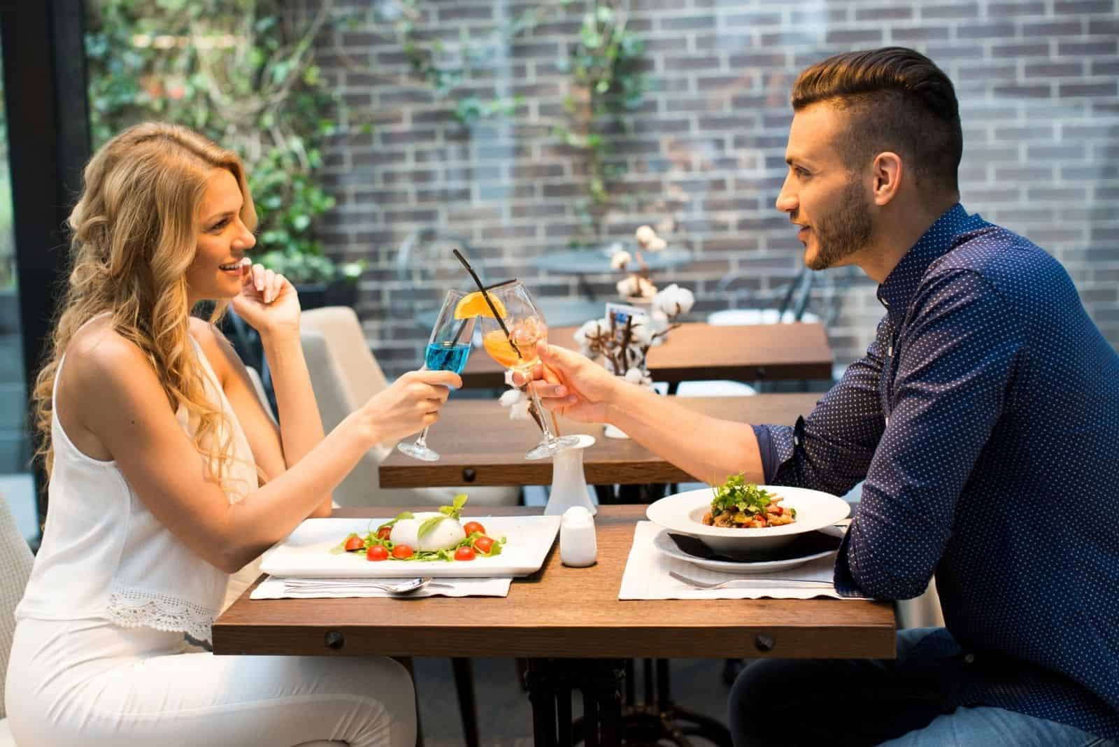 beautiful couple in a date at a restaurant clinking their wine glass