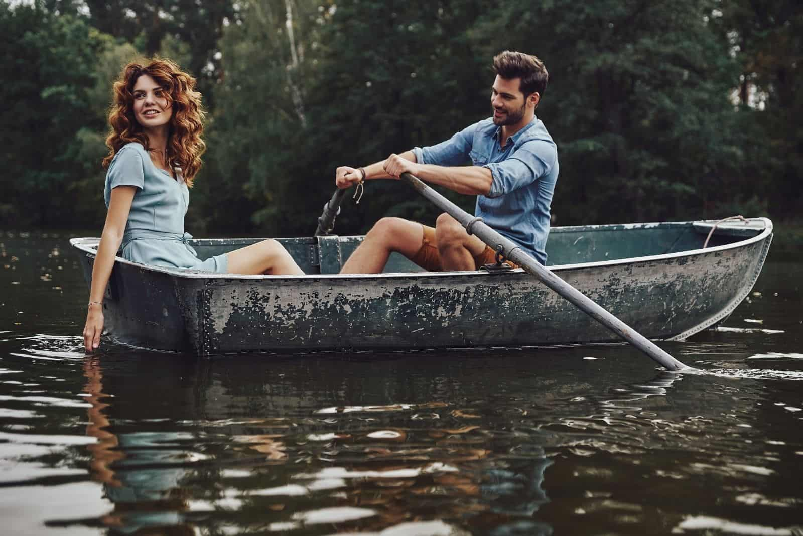 beautiful young couple enjoying riding a boat while rowing a boat