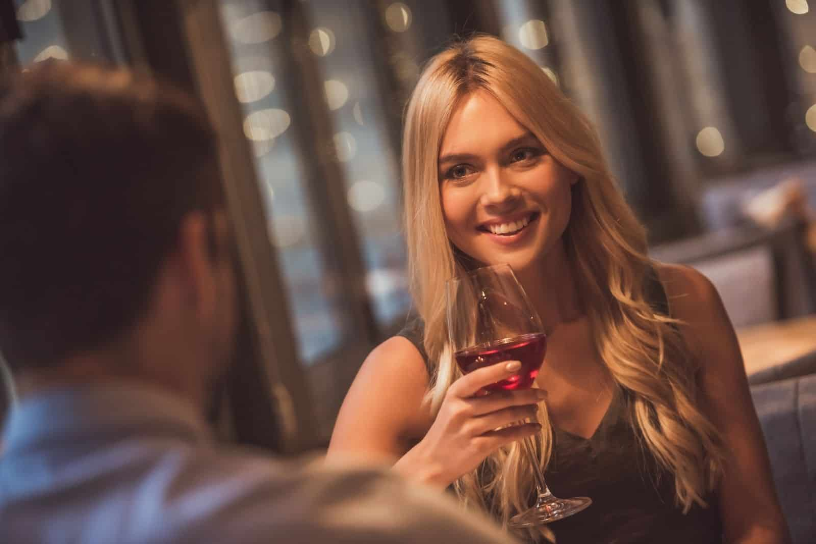 beautiful young woman looking at her date while holding a wine of glass
