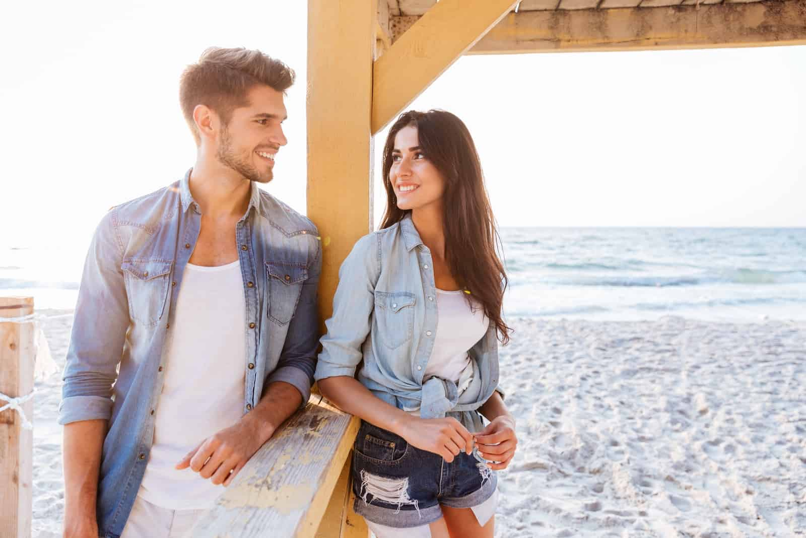 man and woman flirting while standing on the beach