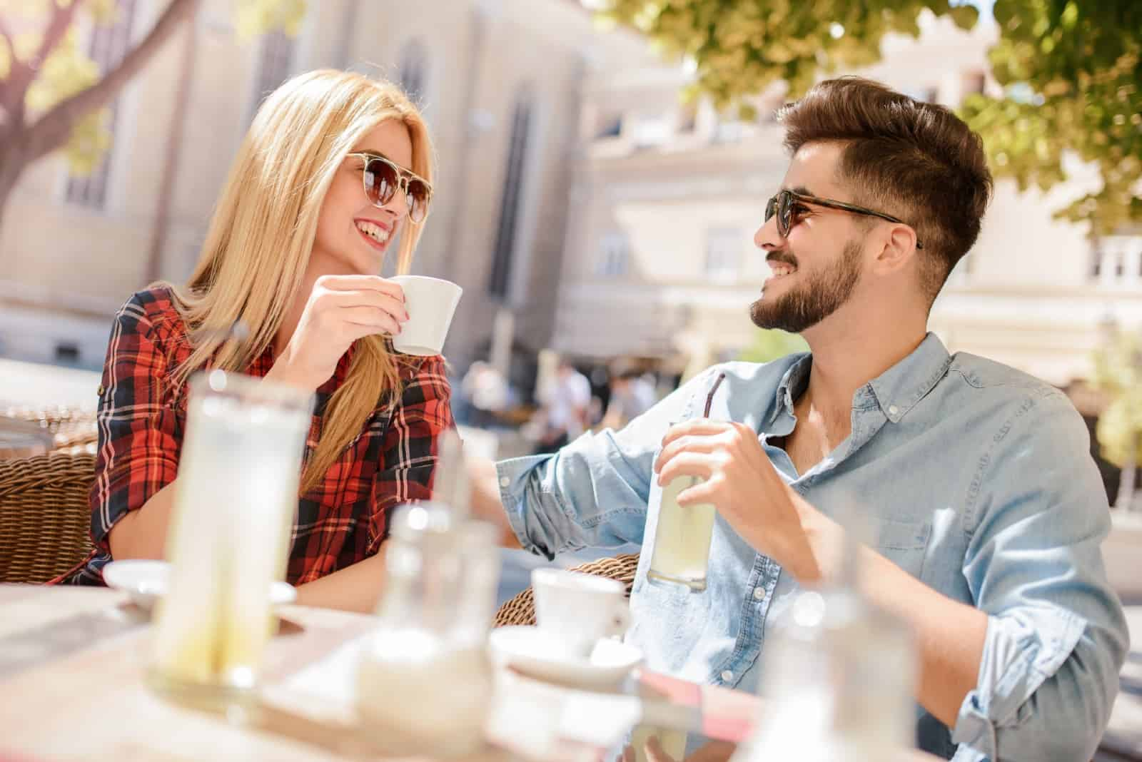 man and woman having coffee while sitting in cafe outdoor