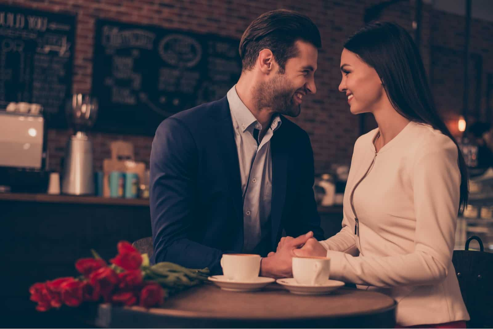 man and woman holding hands while sitting in cafe