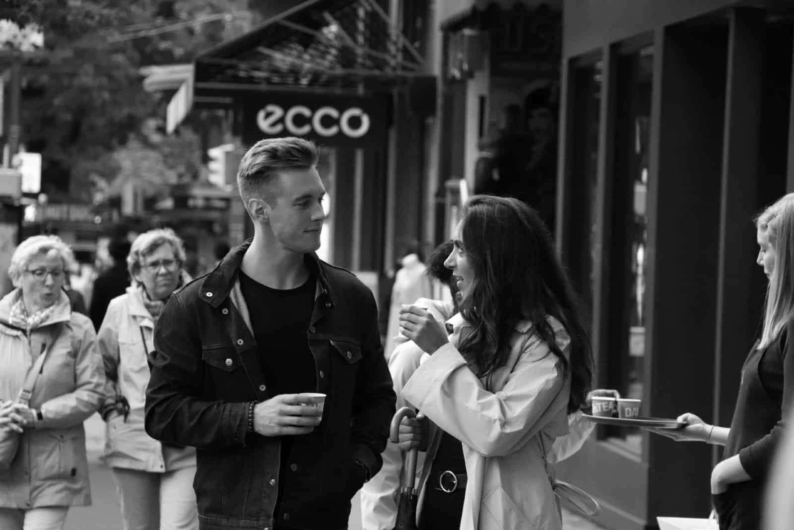 man and woman making eye contact while having coffee outdoor
