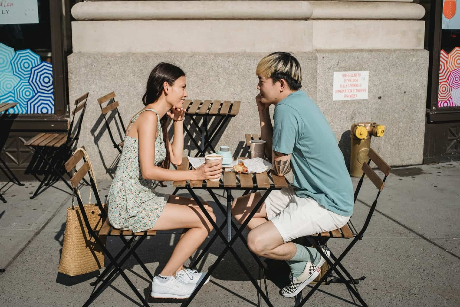 man and woman making eye contact while sitting at table outdoor
