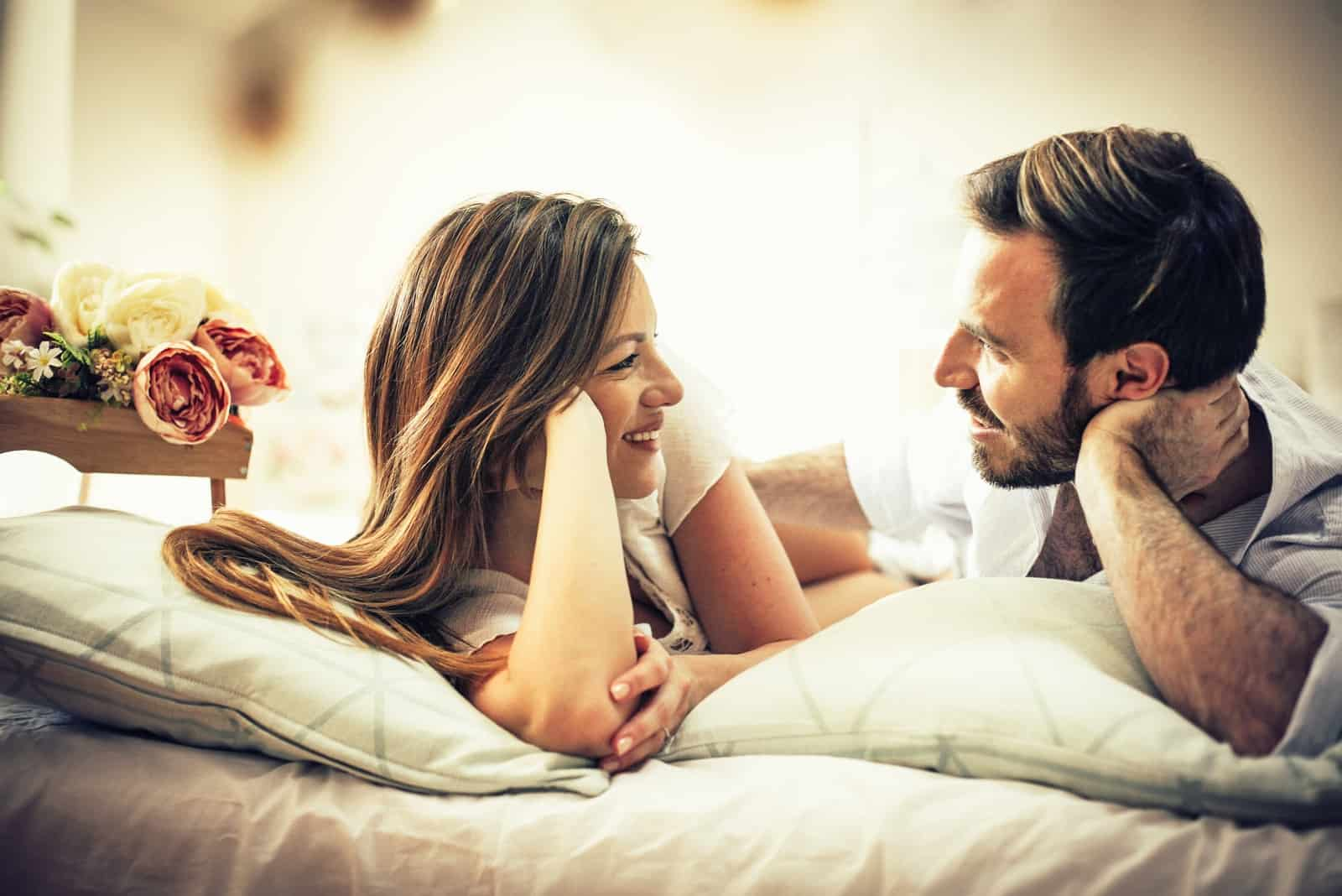 man and woman making eye contact while laying on bed