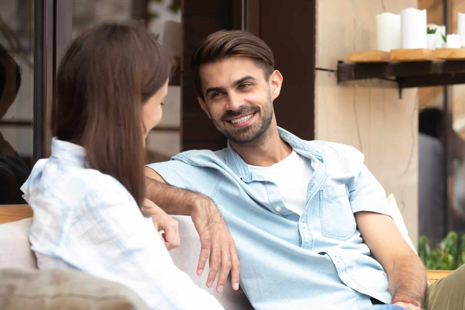 happy man in blue shirt and woman sitting near storefront