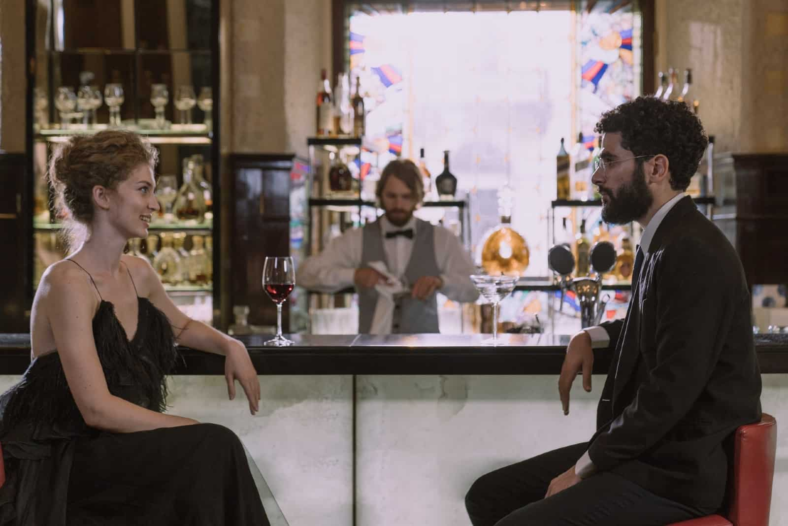 man and woman making eye contact while sitting on bar chairs in bar