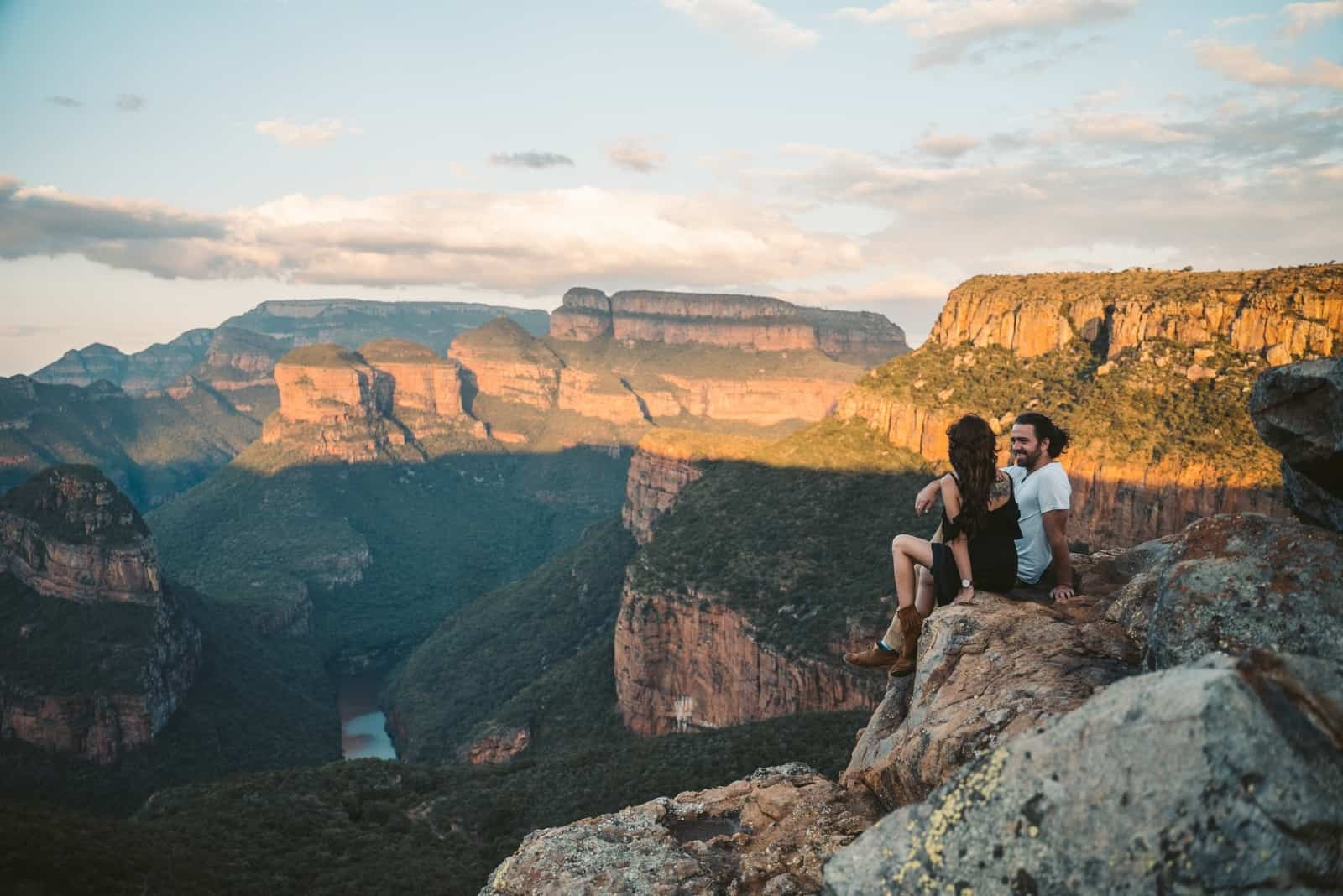 man and woman talking while sitting on rock
