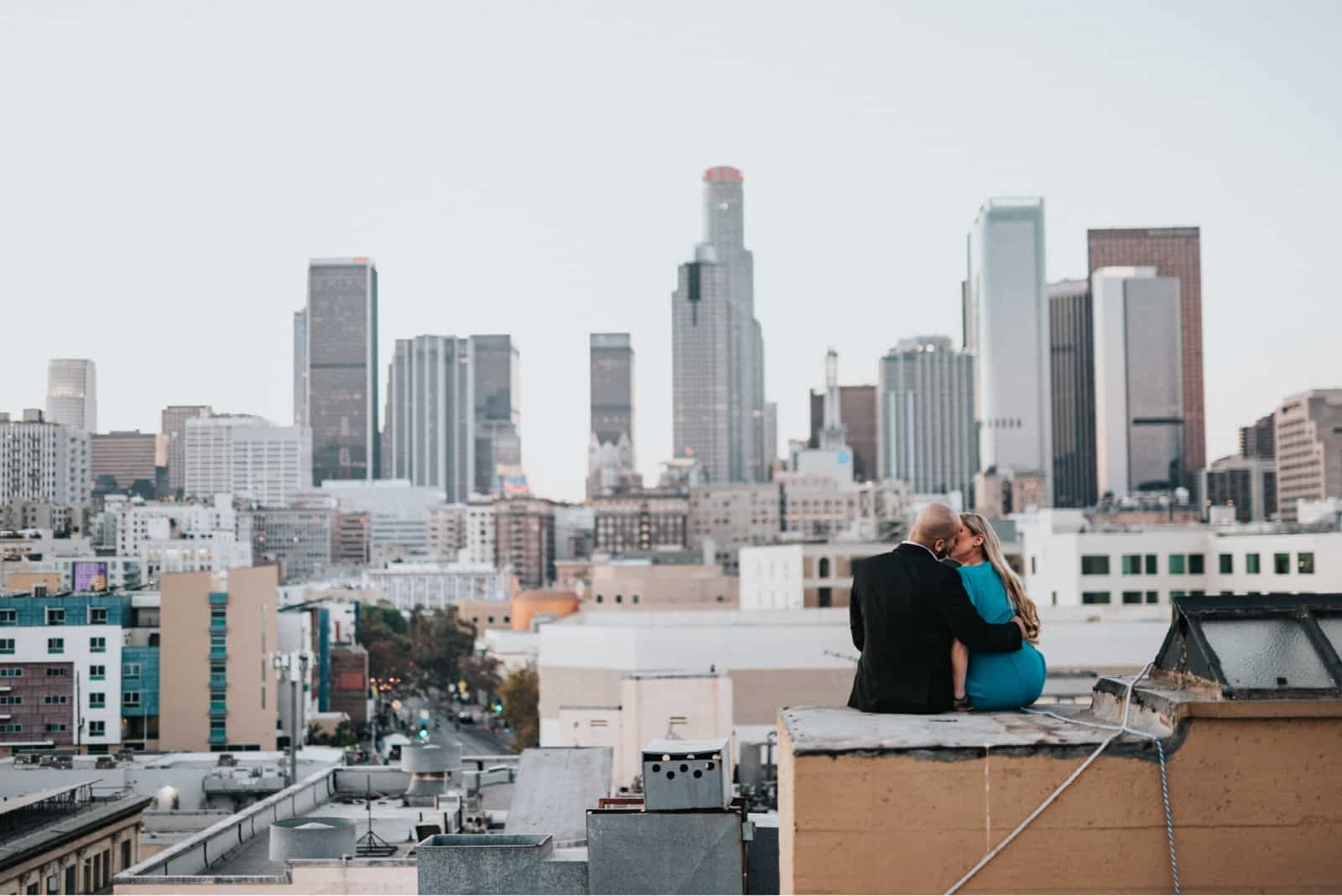 man and woman kissing while sitting on rooftop