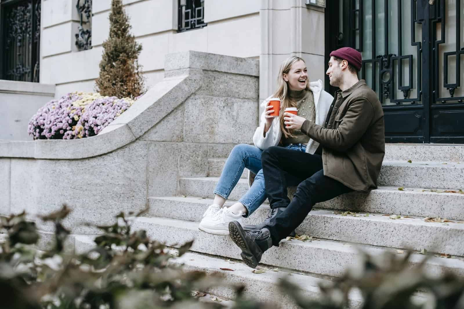 man and woman having coffee while sitting on stairs