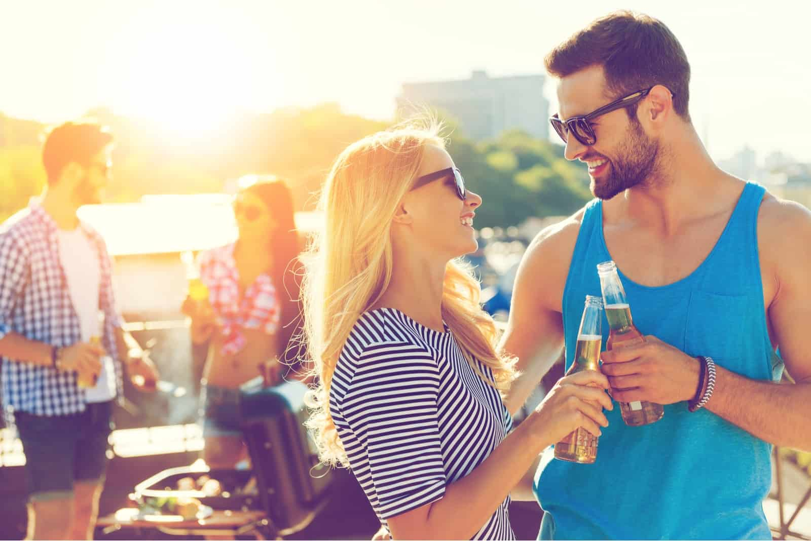 man and woman smiling while drinking drinks outdoor