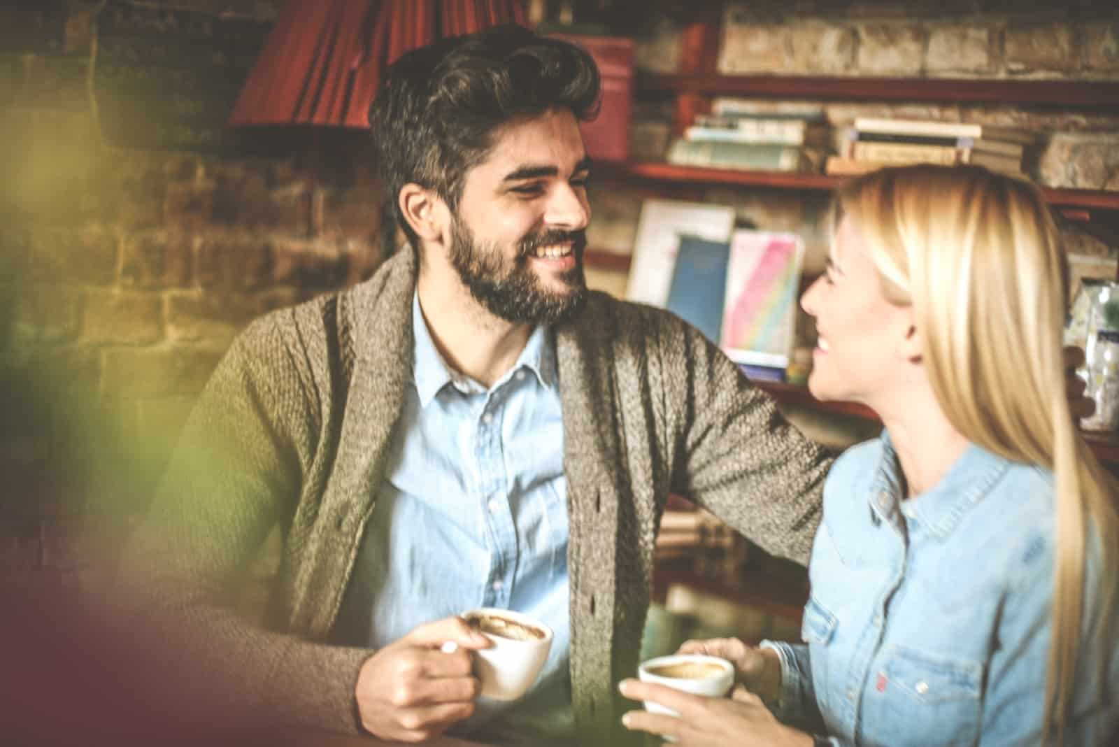 man and woman smiling while having coffee