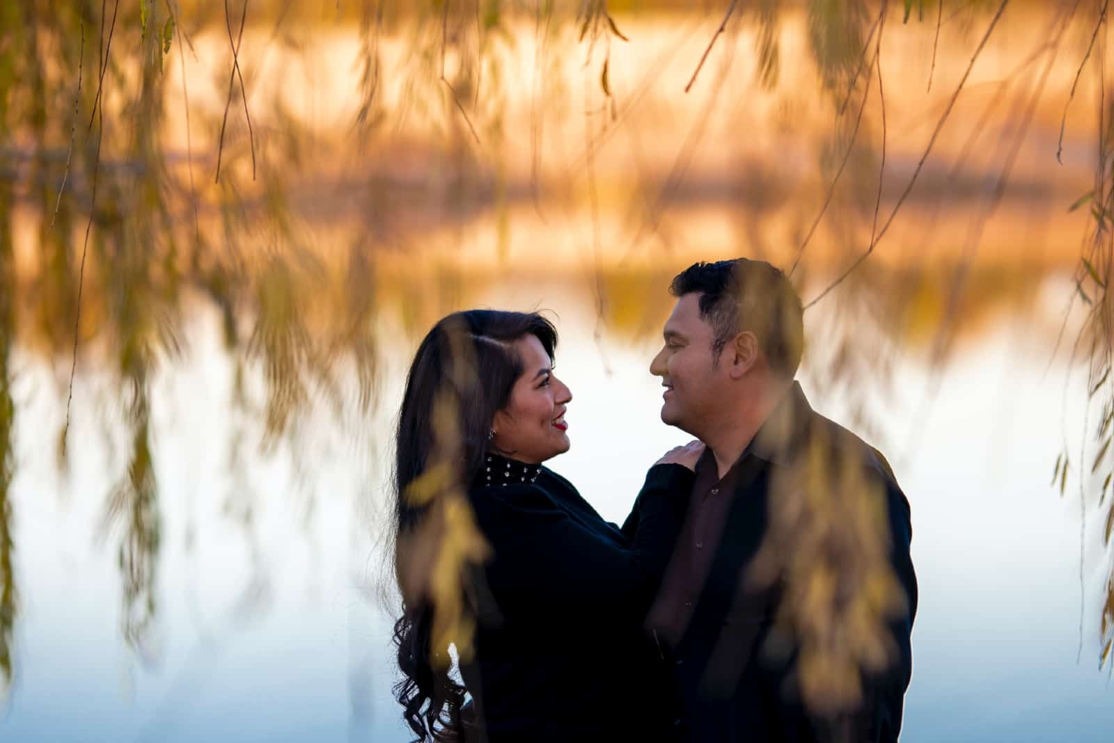 man and woman making eye contact while standing near water