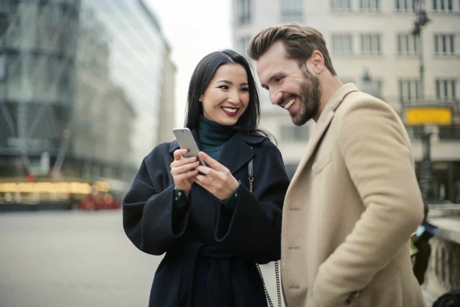 man and woman looking at phone while standing on the street