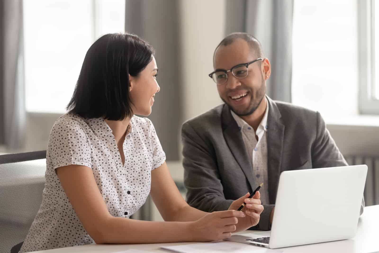 man and woman talking while sitting in office