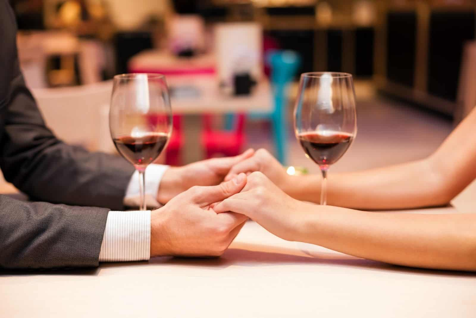 focus image on holding hands of a couple during a dinner date