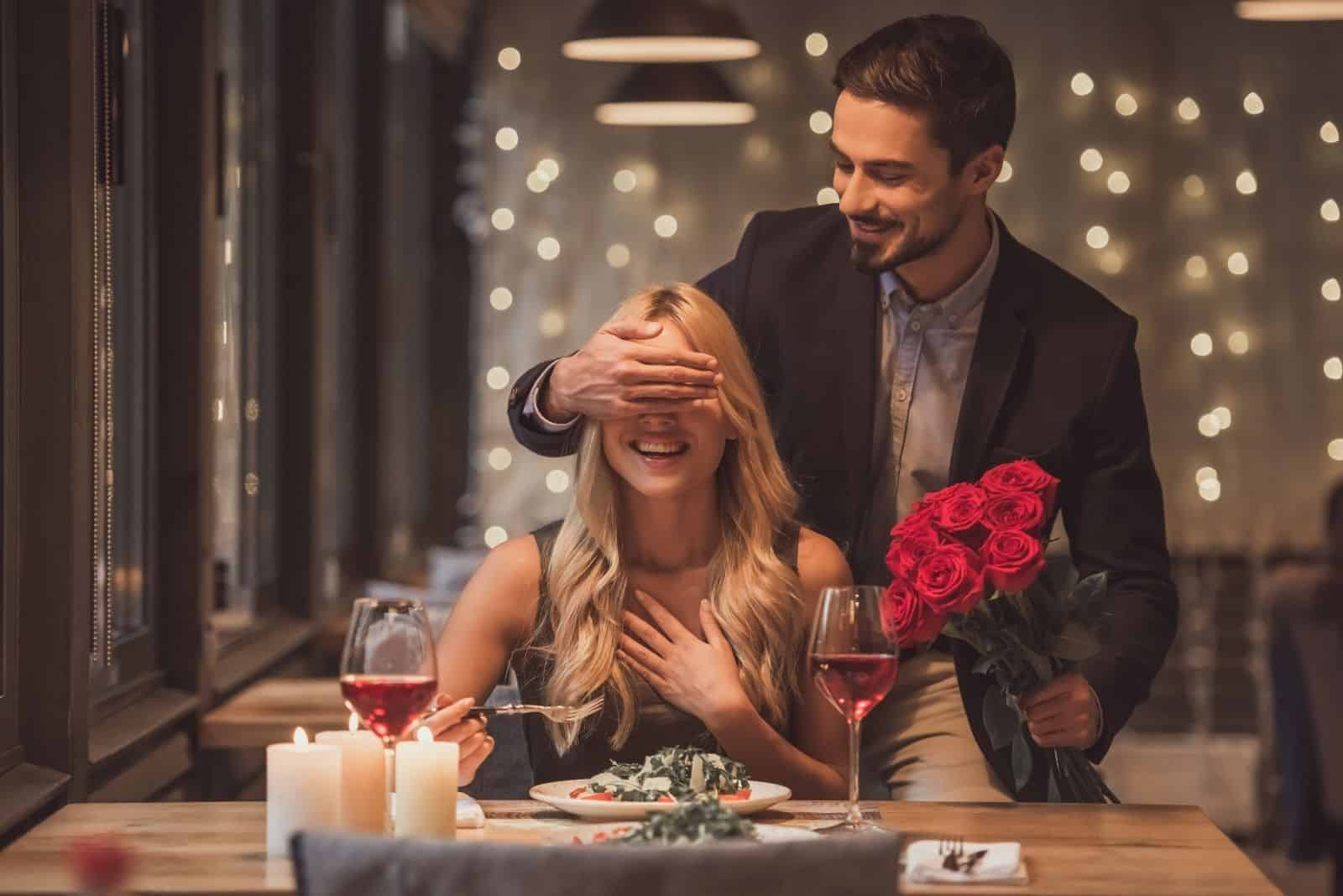 handsome elegant man bringing flowers and surprising his woman waiting in the restaurant