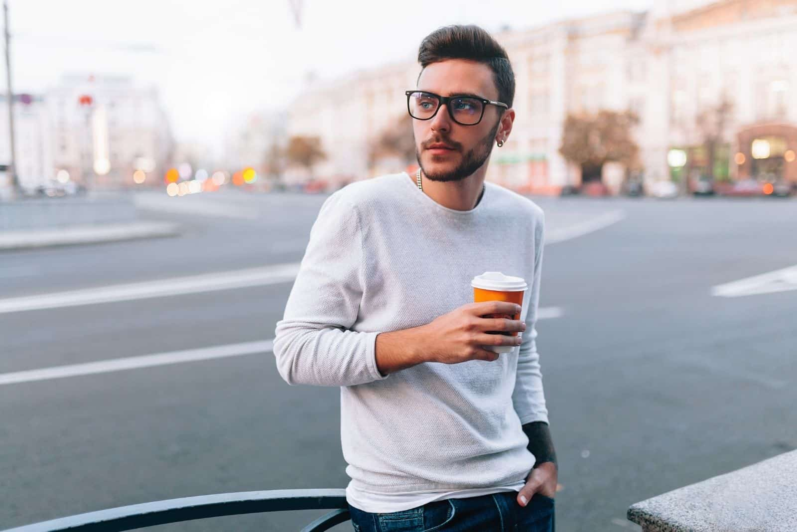 hipster man standing in the street and holding a cup of coffee