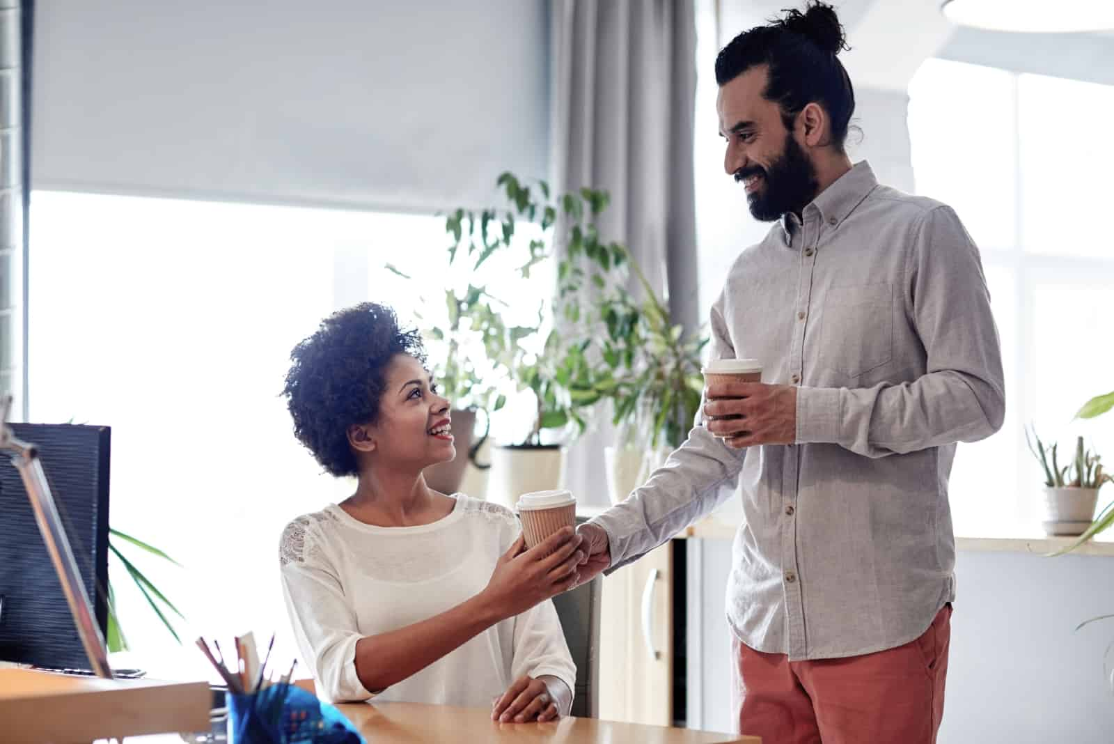 man giving coffee to woman while standing in the office