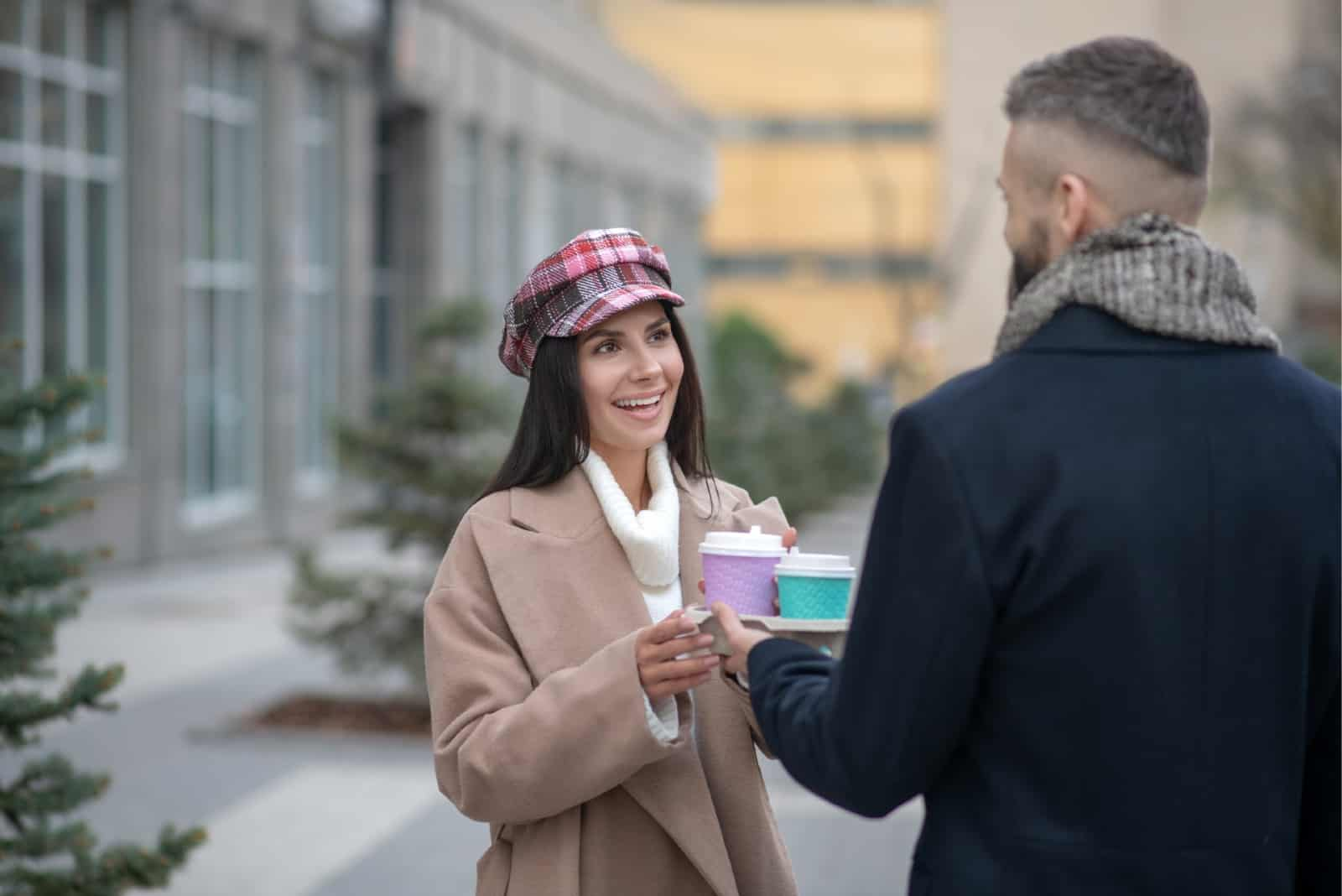 man giving paper cup of coffee to woman