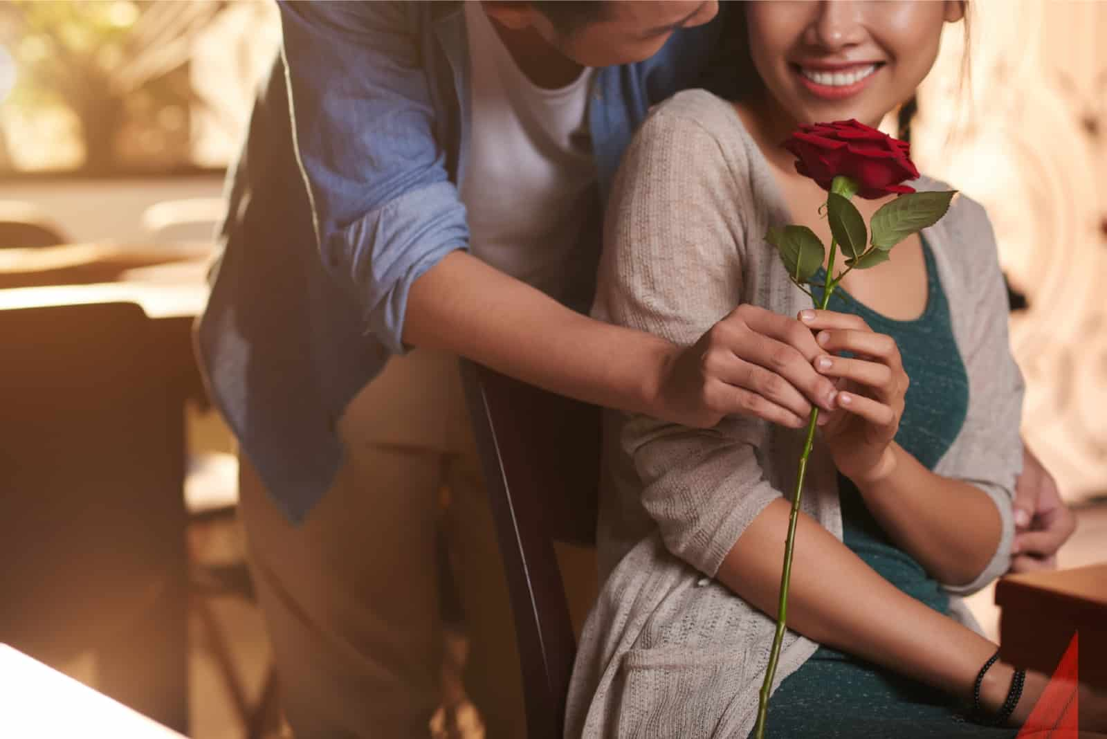 man giving red rose to happy woman