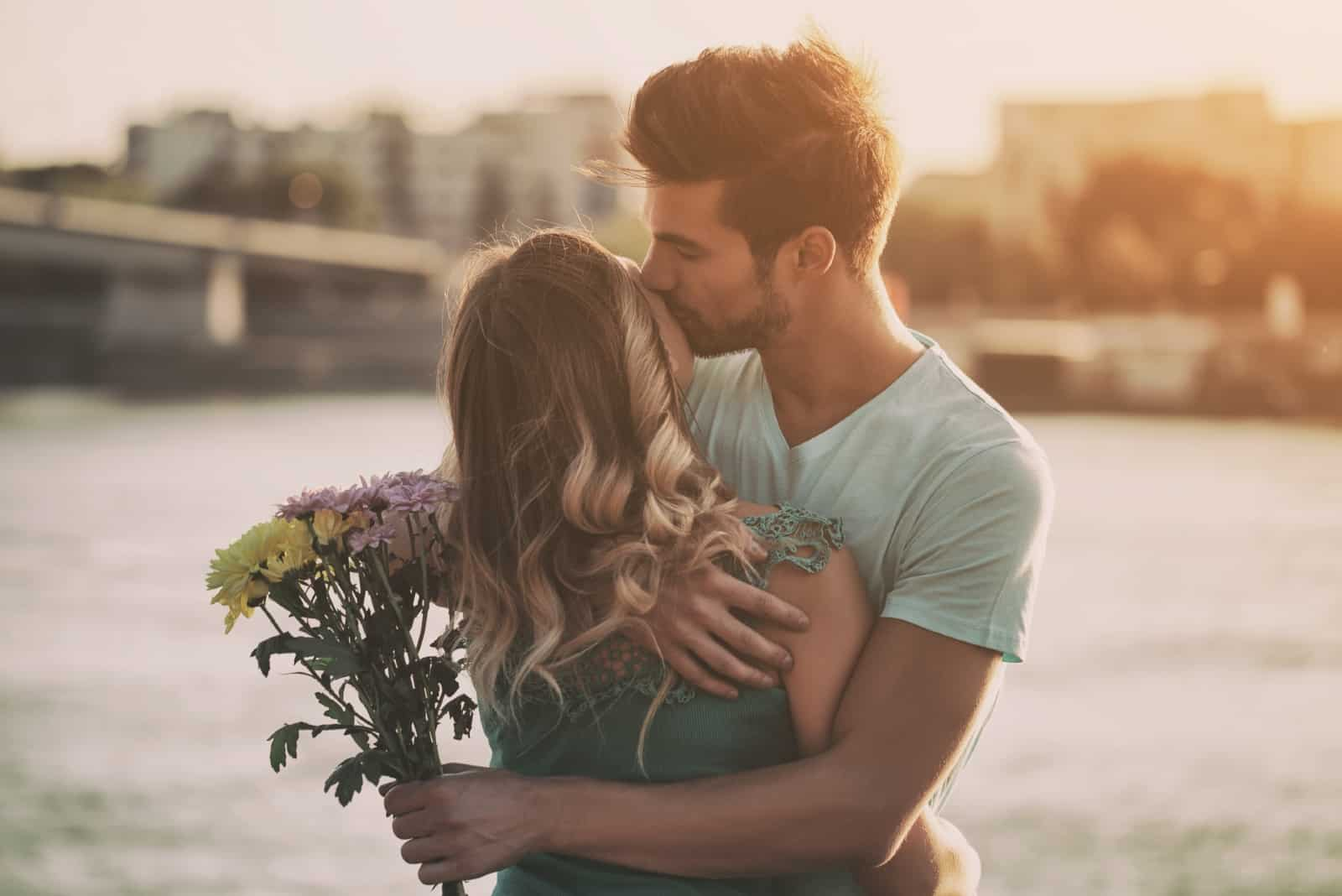 man holding bouquet of flowers while kissing woman