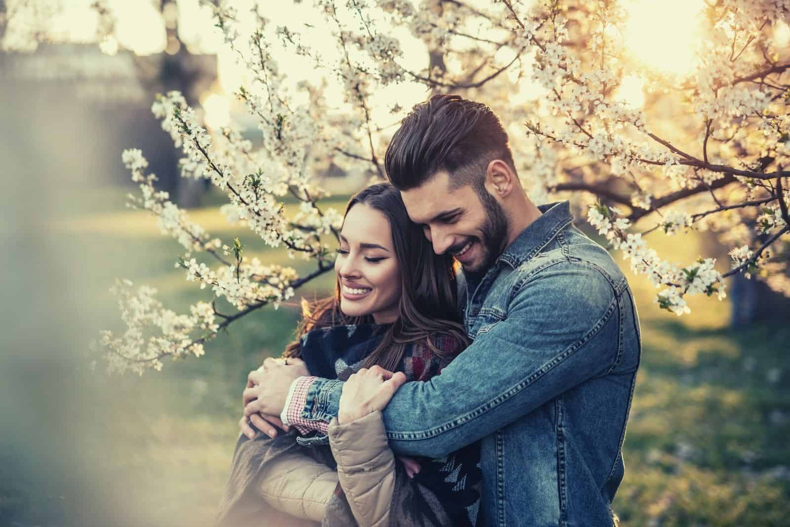man hugging sweetly his girlfriend in the flower garden