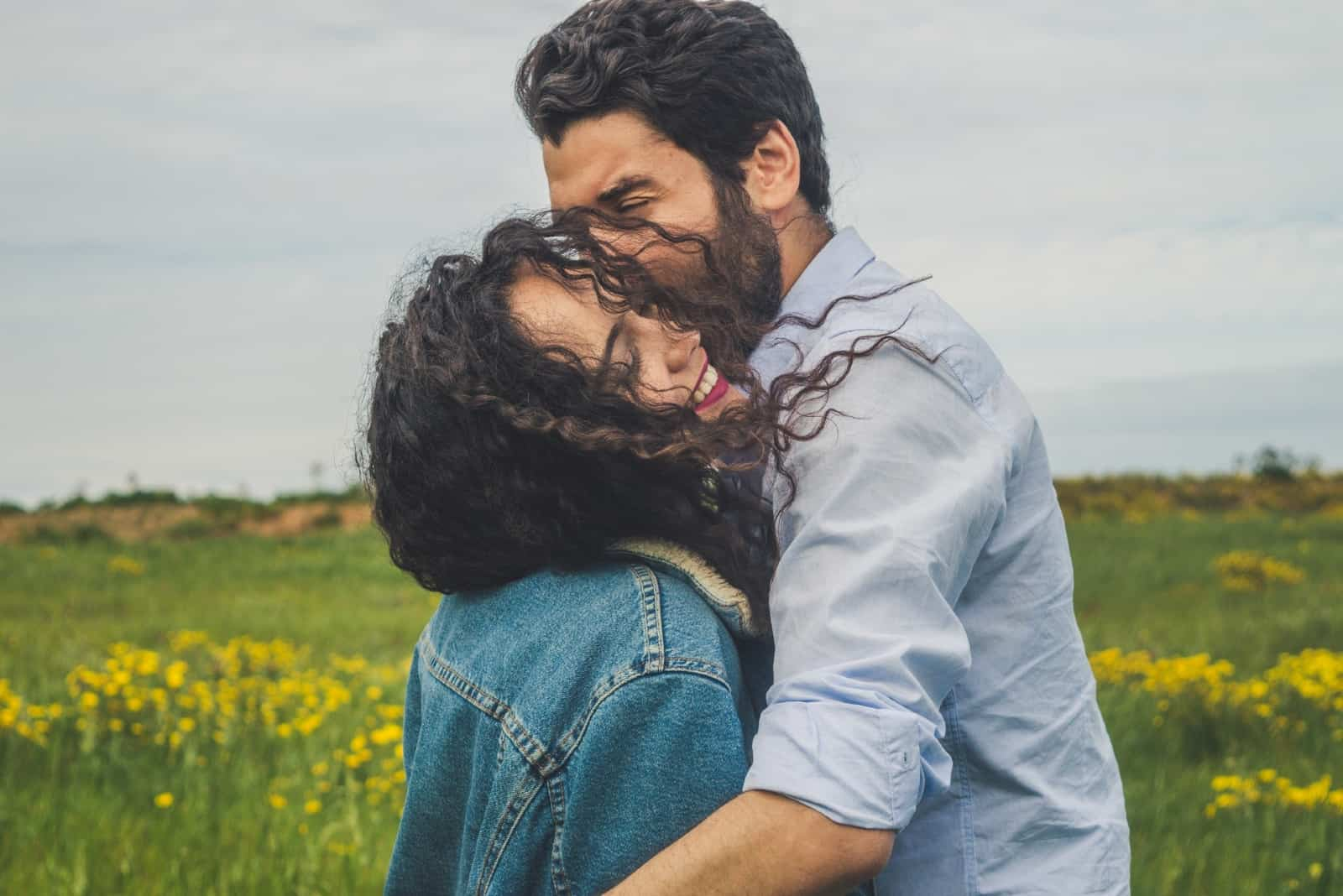 man kissing woman while standing in the field