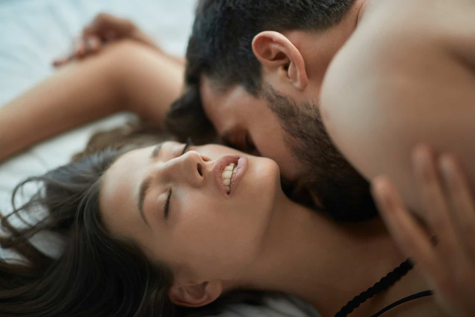 man kissing woman's neck while laying on bed