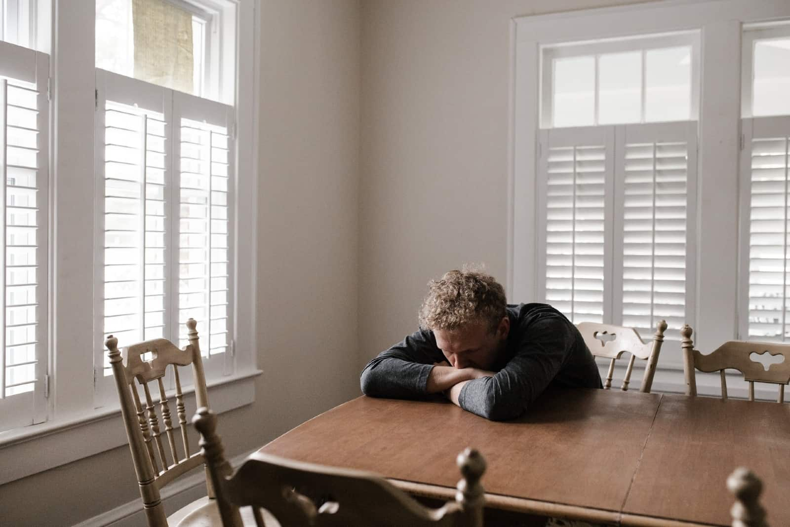 sad man in black top leaning on table