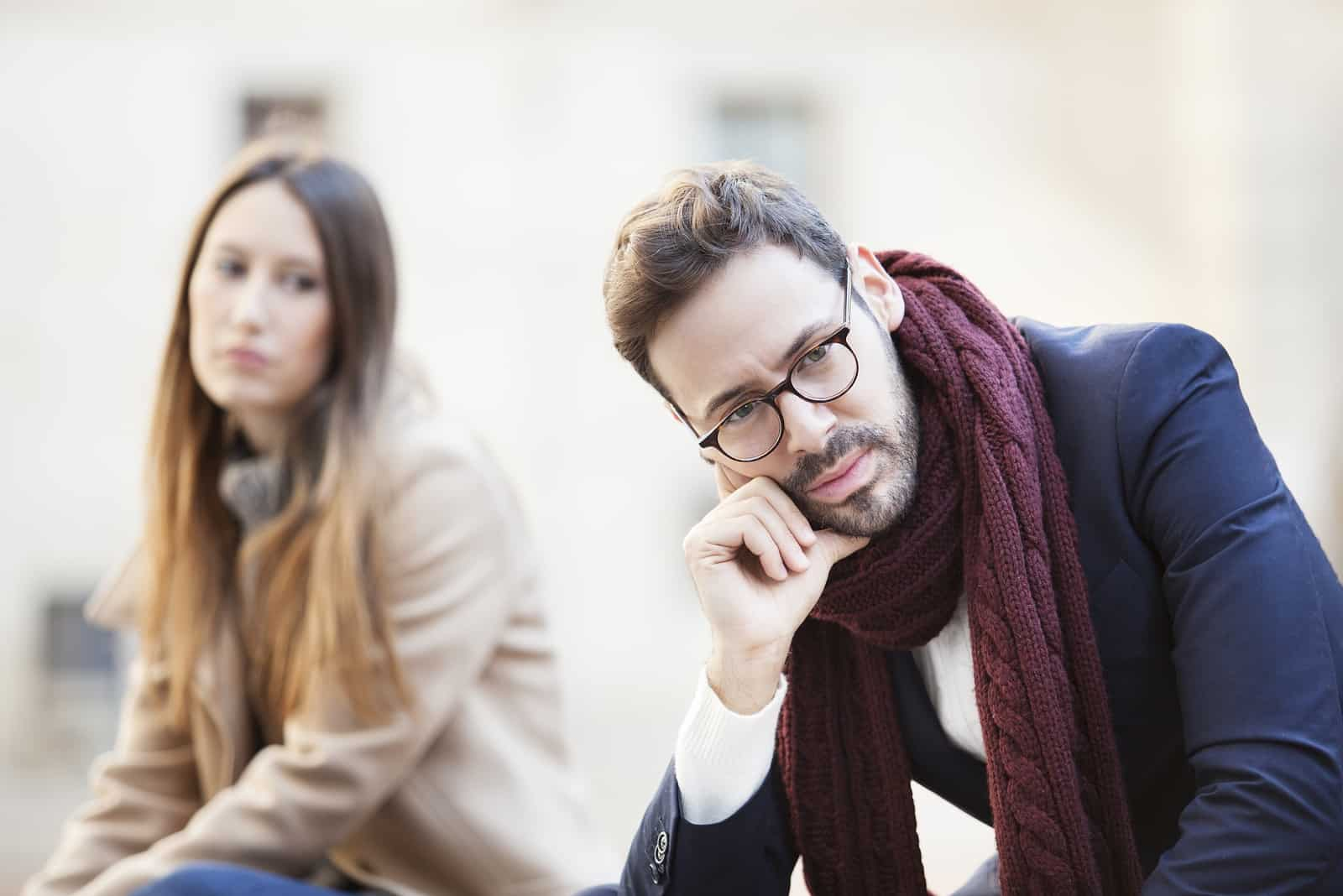 pensive man with eyeglasses sitting near woman outdoor