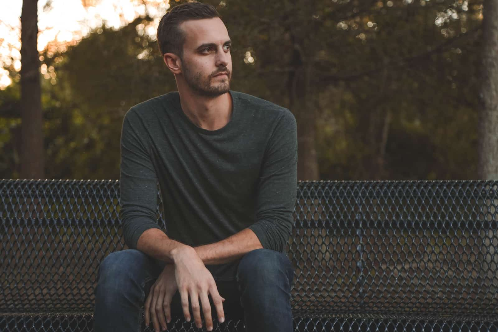 serious man in gray shirt sitting on bench