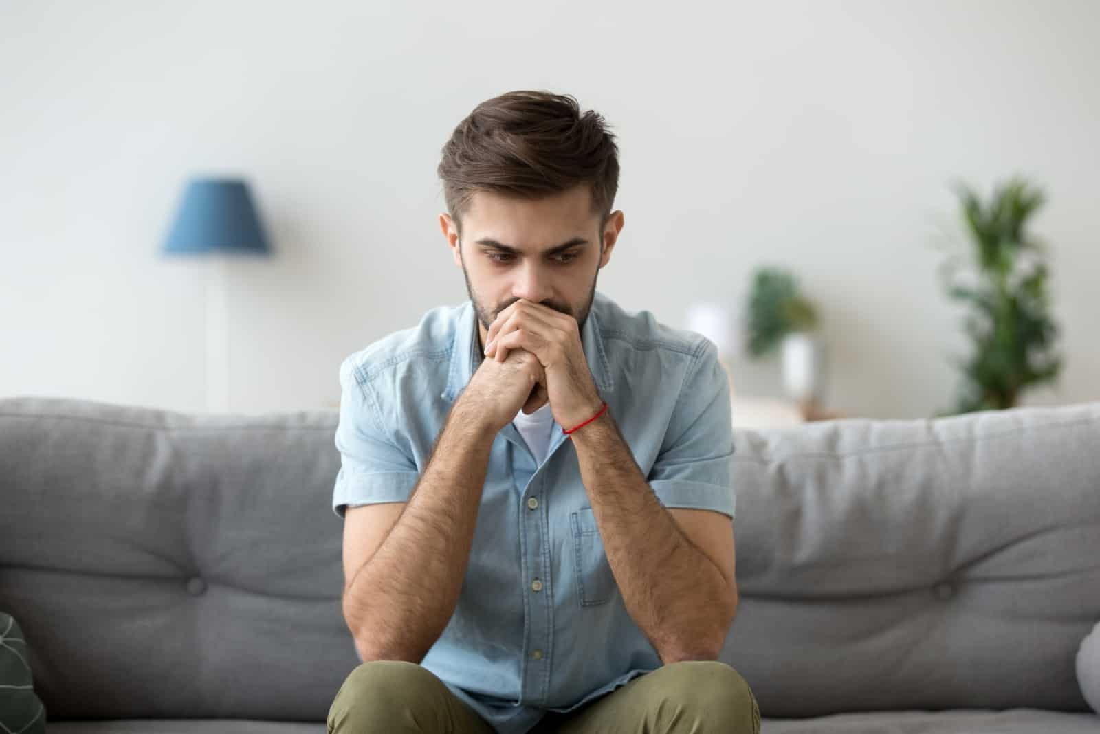 pensive man in blue shirt sitting on sofa