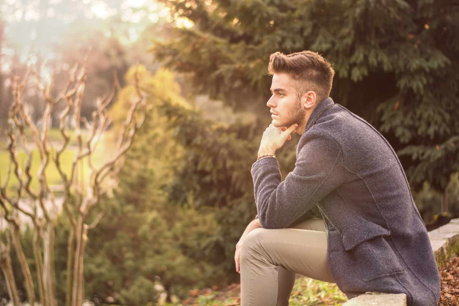 pensive man in gray jacket sitting outdoor