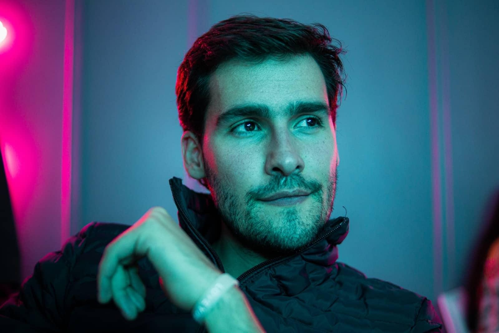 man smiling while sitting near neon light