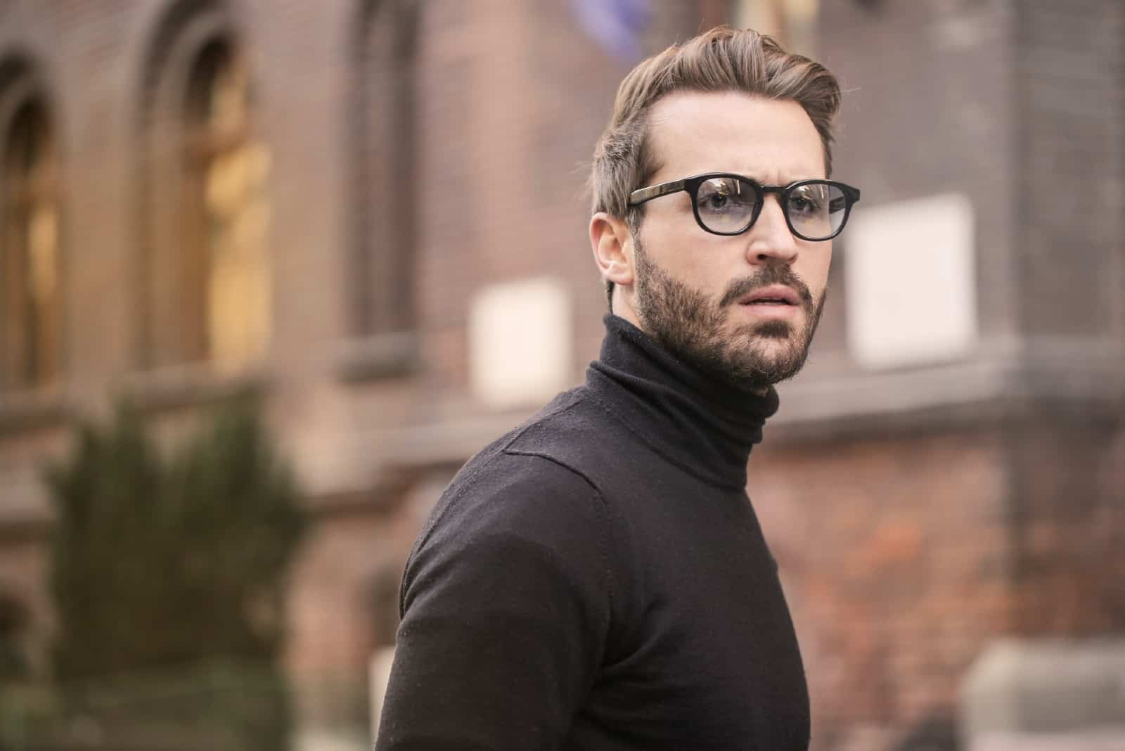 man in black roll neck sweater standing near building